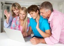 Familj som hemma använder bärbar dator Fotografering för Bildbyråer