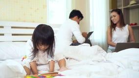 Familj som hemma använder den smartphonebärbara datorn och anteckningsboken