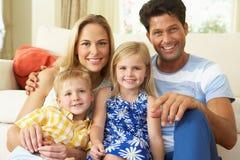 Familj som hemma kopplar av på sofaen Fotografering för Bildbyråer