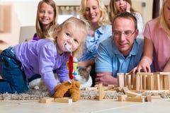 Familj som hemma leker Arkivbild