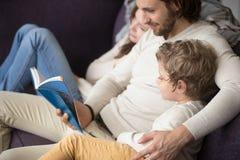 Familj som hemma sitter på soffan med en bok arkivbild