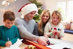 Familj som hemma slår in julgåvor Royaltyfri Bild