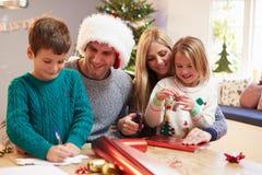 Familj som hemma slår in julgåvor Arkivbilder