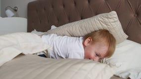 Familj som hemma spenderar fri tid Gladlynt familj som har gyckel med deras döttrar på sängen arkivfilmer