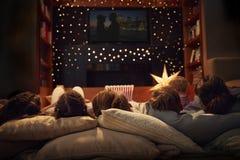 Familj som hemma tycker om filmnatt tillsammans royaltyfria foton