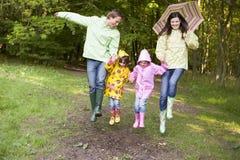 familj som hoppar over utomhus det le paraplyet Royaltyfri Foto
