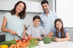 Familj som hugger av grönsaker i kök Royaltyfri Fotografi