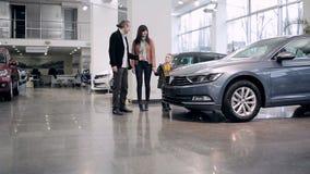 Familj som intresseras av en bil i visningslokal stock video