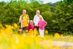 Familj som joggar i ängen för kondition Arkivfoto