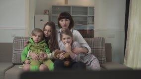 Familj som känslomässigt sitter på soffan i gästrummet och den hållande ögonen på TV:N Äldre systrar och det mer unga syskonet sp arkivfilmer