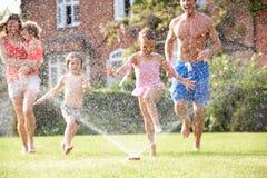 Familj som kör till och med den trädgårds- sprinkleren Royaltyfria Bilder