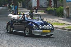 Familj som kör Volkswagen Beetle på det retrocar loppet Arkivbild