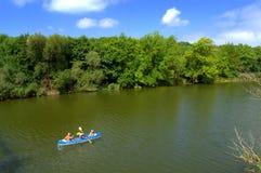 Familj som kanotar på floden Arkivfoton