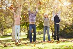 Familj som kastar Autumn Leaves In The Air Royaltyfri Bild
