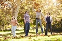 Familj som kastar Autumn Leaves In The Air royaltyfria foton