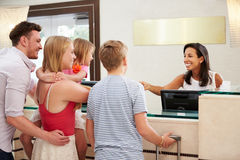 Familj som in kontrollerar på hotellmottagandet Royaltyfri Fotografi