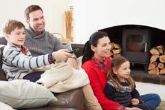 Familj som kopplar av hållande ögonen på inomhus television tillsammans arkivbilder