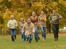 Familj som kopplar av i höstskog Arkivfoton