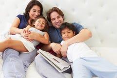 Familj som kopplar av i säng med kaffe och tidningen Arkivfoto
