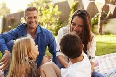 Familj som kopplar av på filten i trädgård royaltyfria bilder