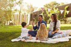 Familj som kopplar av på filten i trädgård royaltyfri fotografi