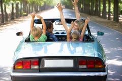 Familj som kör along i en sportbil Fotografering för Bildbyråer