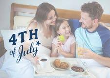 familj som kyler på sängen för 4th Juli Arkivbilder