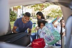 Familj som lämnar för semesterpäfyllningsbagage in i bilen royaltyfri foto