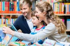Familj som läser en bok i arkivet royaltyfria bilder