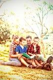 Familj som läser en bok i parkera royaltyfria foton
