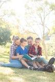 Familj som läser en bok i parkera arkivfoton