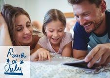 Familj som läser en bok som ligger på säng för 4th Juli Arkivfoton