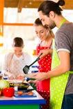 Familj som lagar mat sund mat i inhemskt kök Royaltyfria Bilder