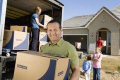Familj som lastar av leveransen Van By New House royaltyfria foton