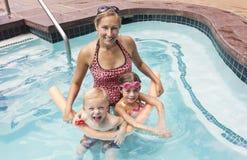 Familj som leker i simbassängen Royaltyfria Bilder