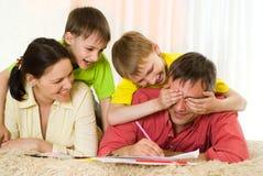 Familj som leker på mattan Royaltyfria Bilder