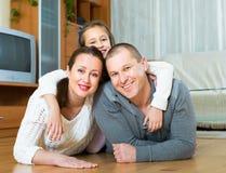 Familj som ler på golvet Fotografering för Bildbyråer