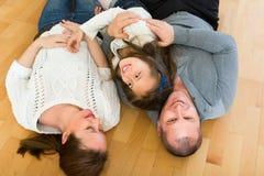 Familj som ler på golvet Arkivbilder