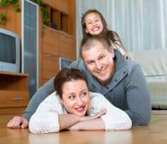 Familj som ler på golvet Arkivbild