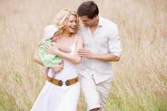 familj som ler utomhus att gå Fotografering för Bildbyråer