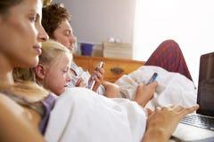 Familj som ligger i säng som använder tillsammans Digital apparater royaltyfria bilder