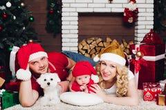 Familj som ligger på golv nära spisen med den lilla sonen och hunden och ler på kameran royaltyfri fotografi