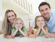 Familj som ligger på golvet Arkivbild