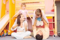 Familj som ligger på golvet Royaltyfria Bilder