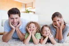Familj som ligger på en matta Royaltyfria Bilder
