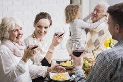 Familj som lyfter exponeringsglas i ett rostat bröd royaltyfria bilder