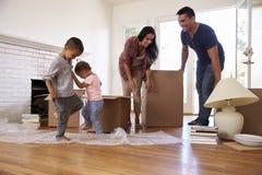 Familj som packar upp askar i nytt hem på rörande dag Arkivbilder