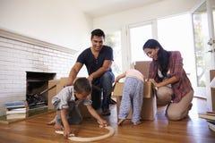 Familj som packar upp askar i nytt hem på rörande dag royaltyfri fotografi