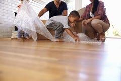 Familj som packar upp askar i nytt hem på rörande dag arkivfoton