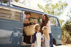 Familj som packar upp deras campareskåpbil för en semester för vägtur Arkivfoton